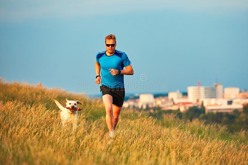 Sport lifestyle with dog. Athletic young man and labrador retriever are running on the hillside outside the city. Prague, Czech Republic royalty free stock image