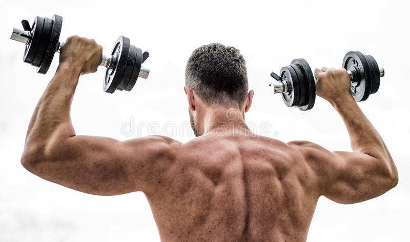 Sport lifestyle. Dumbbell exercise gym. Muscular man exercising with dumbbell rear view. Actions speak louder than stock image