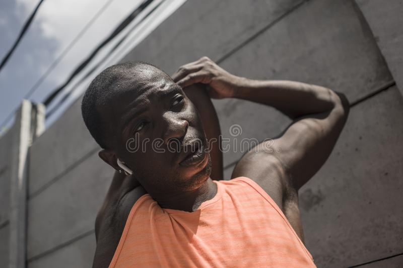 Young attractive and athletic black afro American man stretching arms and upper torso ready for running workout looking focused. Sport lifestyle portrait of royalty free stock photos
