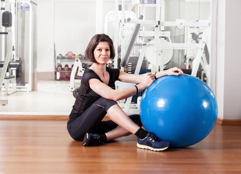Sport love. Young lady with pilates ball in gym posing and looking at camera