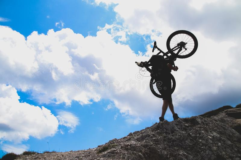 Sport man in action lifting bike on his shoulder on rock mountain with blue sky background. royalty free stock photos