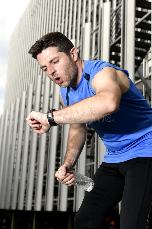 Sport man breathing exhausted after running leaning tired and checking timer watch. Young sport man breathing exhausted after running training on city urban royalty free stock photos