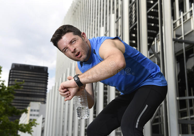 Sport man breathing exhausted after running leaning tired and checking timer watch. Young sport man breathing exhausted after running training on city urban stock images