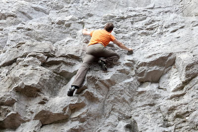 Sport man is climbing. On a grey rock wall royalty free stock image