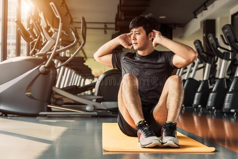 Sport man doing crunch or sit up posture on yoga mat in fitness gym at condominium with gym equipment background. Office working royalty free stock photography