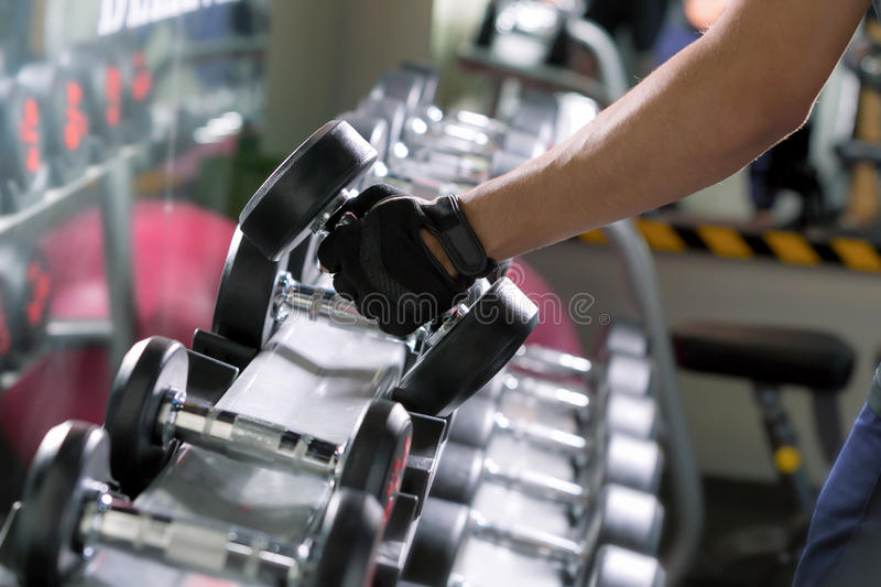 Sport man doing one-arm dumbbell rows of metal in modern gym. stock photography