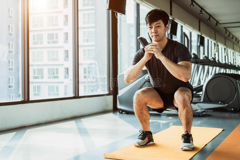 Sport man doing squat posture on yoga mat in fitness gym at condominium in urban. People lifestyles and Sport workout concept.  royalty free stock photography