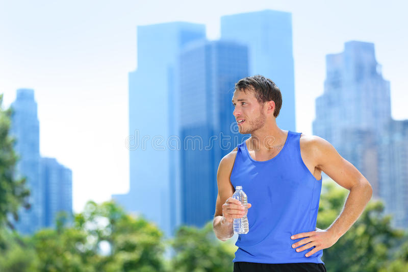 Sport man drinking water bottle in New York City. Male runner sweaty and thirsty after run in Central Park, NYC, Manhattan, with urban buildings skyline in the royalty free stock image