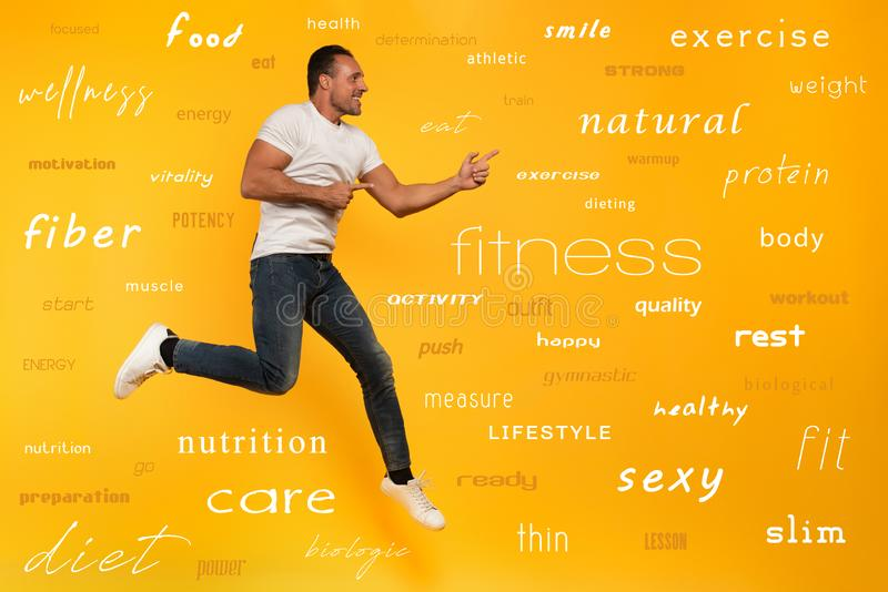 Sport man jumps on a yellow background. Happy and joyful expression. With most important fitness and diet terms. Determinated sport manjumps on a yellow stock images