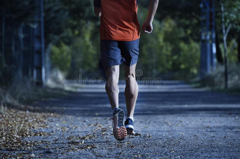 Sport man with ripped athletic and muscular legs running off road in jogging training workout at countryside in Autumn background stock photo