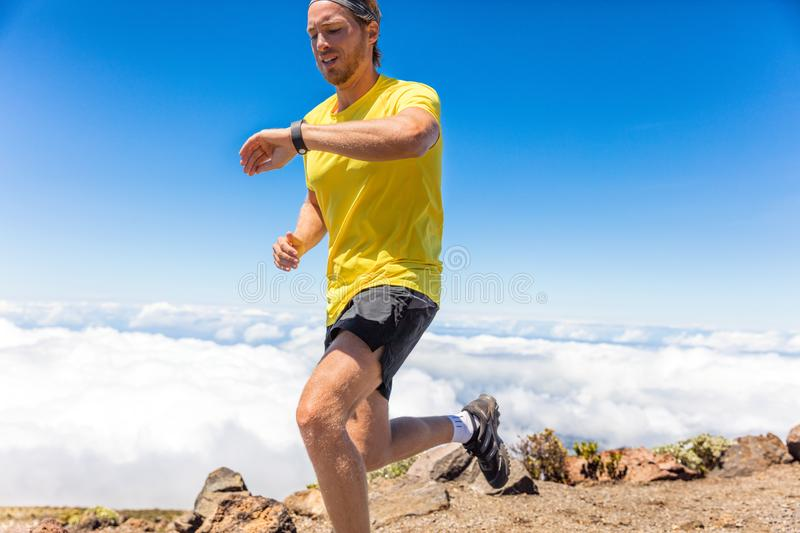 Sport man runner running using smartwatch fitness app on mountain hike trail running summer outdoors. Active sports lifestyle. royalty free stock image