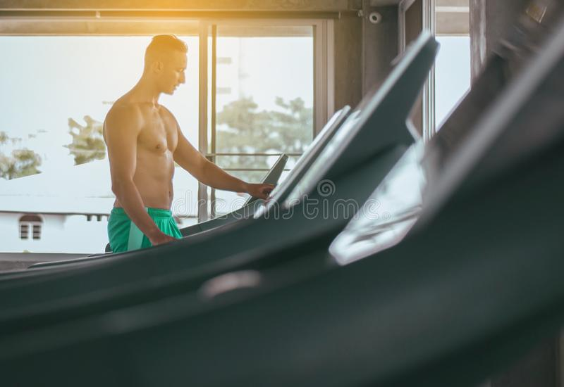Sport man running on treadmills doing cardio training,Cross fit body and muscular in the gym stock images