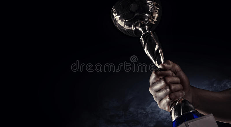 Sport. Man's hand holding up a gold trophy cup royalty free stock image