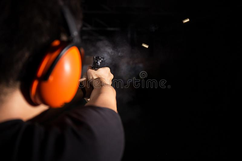 Sport man shooting pistol gun with smoke and fire bullet on black background in shootingrange stock photography