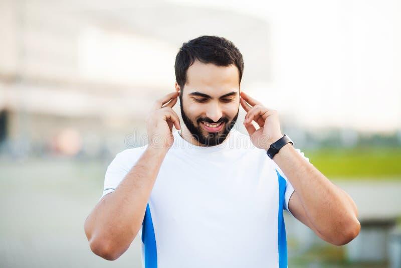 Sport man using headphones for listening music on morning run in park.  stock photos