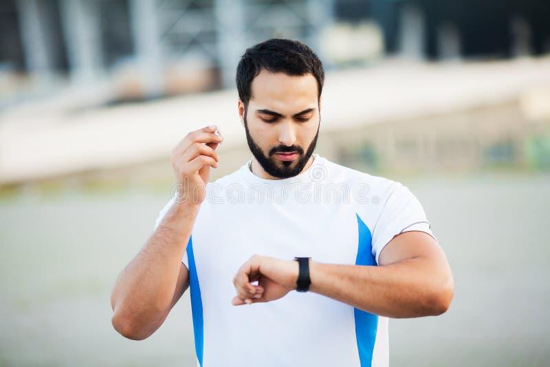 Sport man using headphones for listening music on morning run in park.  stock photography