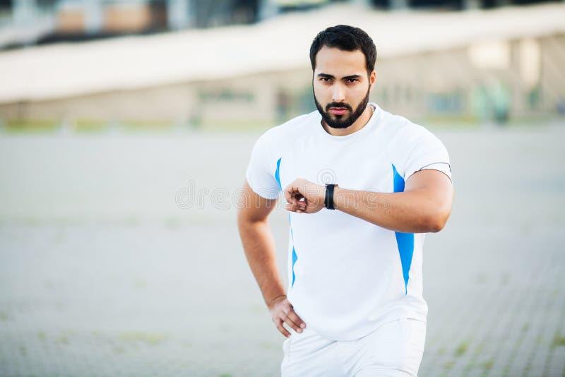 Sport man using headphones for listening music on morning run in park.  royalty free stock photos