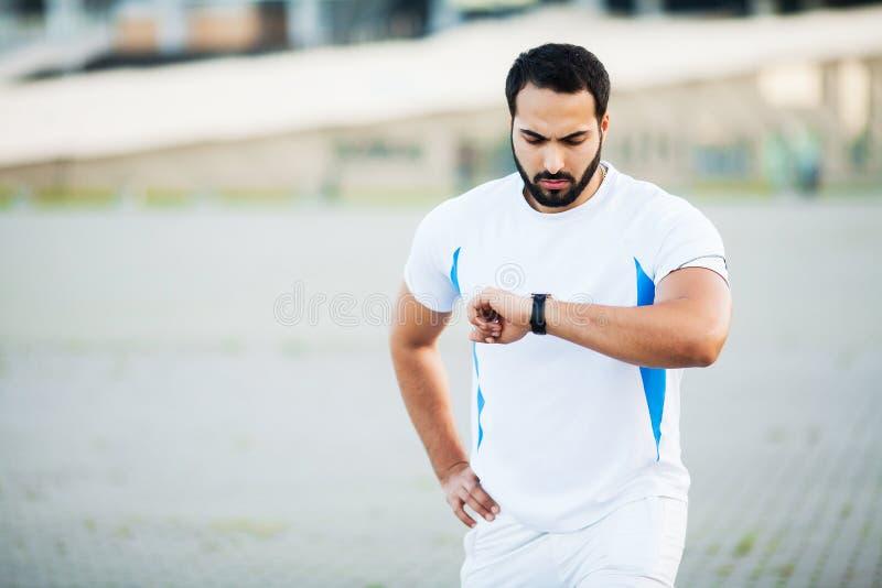 Sport man using headphones for listening music on morning run in park.  stock image