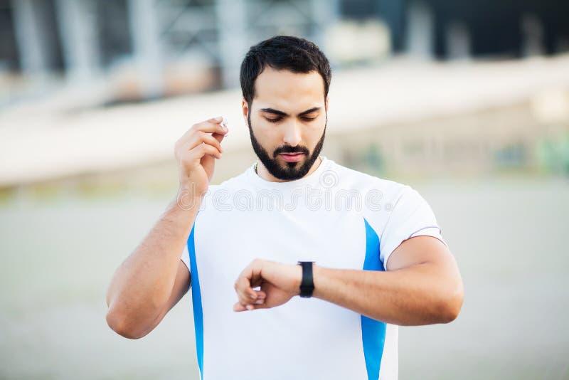 Sport man using headphones for listening music on morning run in park.  royalty free stock image
