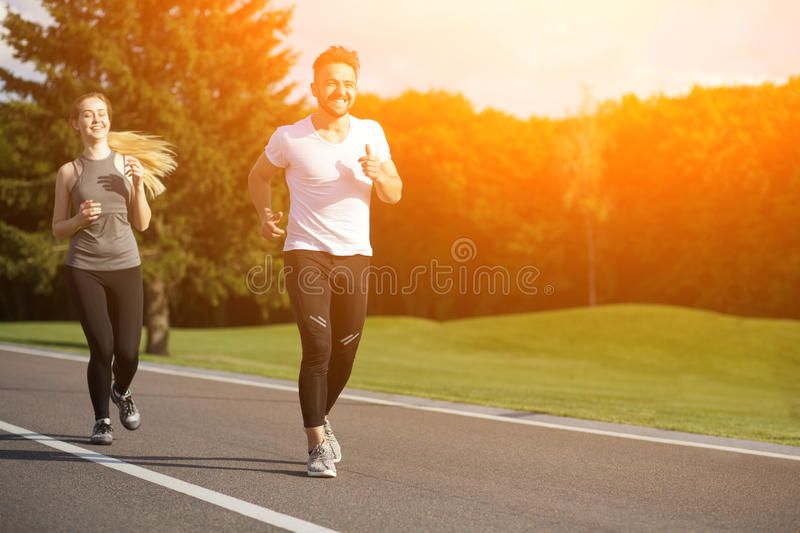 Sport man and woman jogging in park stock photos