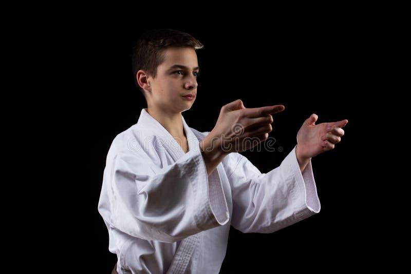 Sport marziale di karatè con il giovane ragazzo in kimono, fondo nero, la gente immagine stock libera da diritti