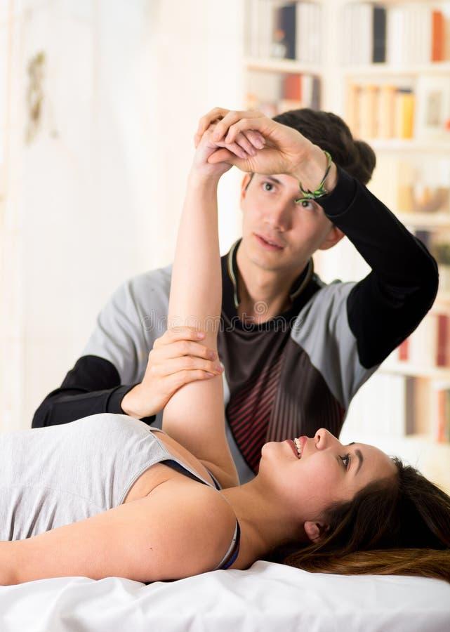 Sport-Massage Hnadsome-Massagetherapeut, der Arme eines weiblichen Athleten, in einem Doktorbürohintergrund massiert lizenzfreies stockbild