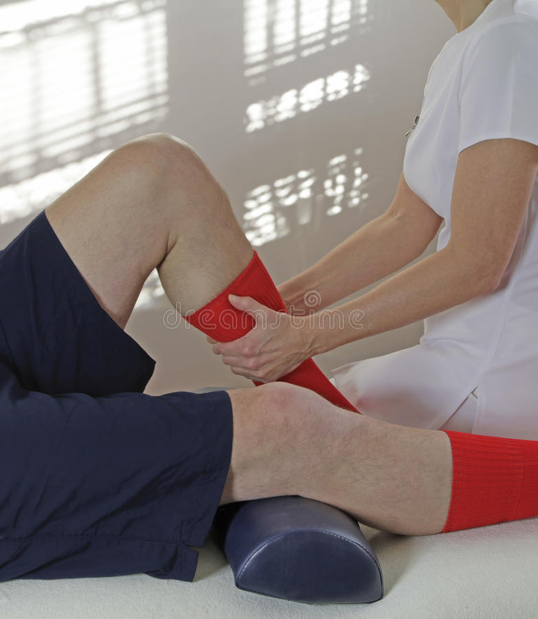 Sport Massage Therapist working on calf muscle. Female sports massage therapist working on a mature male client calf muscle on couch stock photo