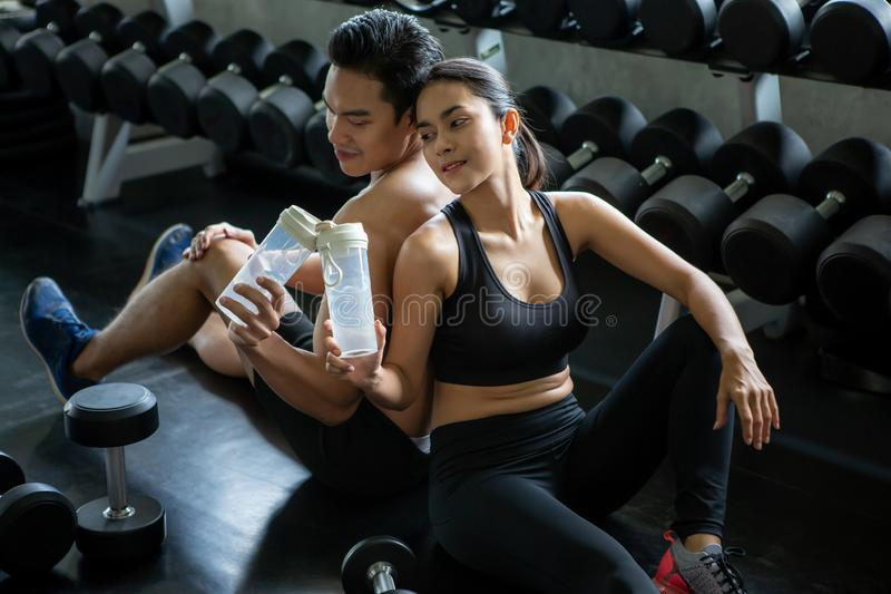 Sport man and woman sitting on floor  tired taking a break drinking water after exercise . workout. asian couple fitness in. Sport men and women sitting on floor royalty free stock photography