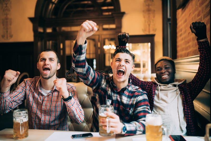 Sport, mensen, vrije tijd, vriendschaps en vermaakconcept - de Multiraciale vrienden groeperen het drinken bier en het vieren ove stock foto