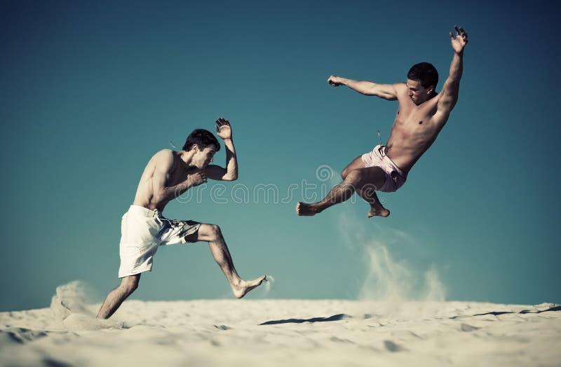 Sport mit zwei jungen Männern, der auf Strand kämpft lizenzfreie stockfotos