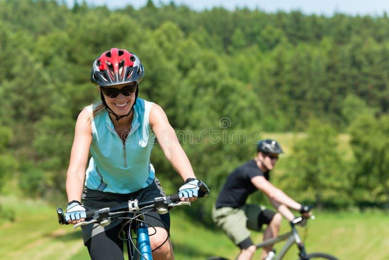 Sport mountain couple biking uphill sunny meadows royalty free stock image