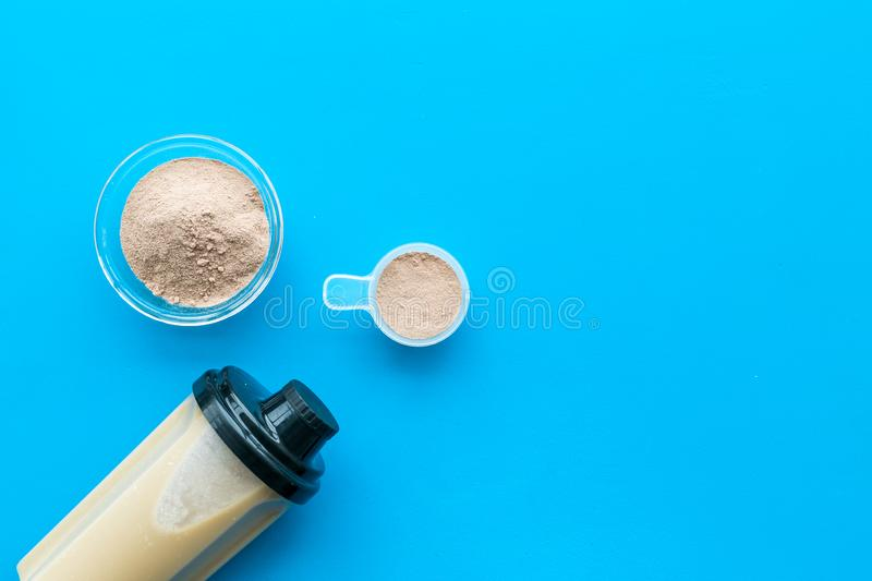 Sport nutrition set with protein powder for cocktail and scoop on blue background top view space for text stock image