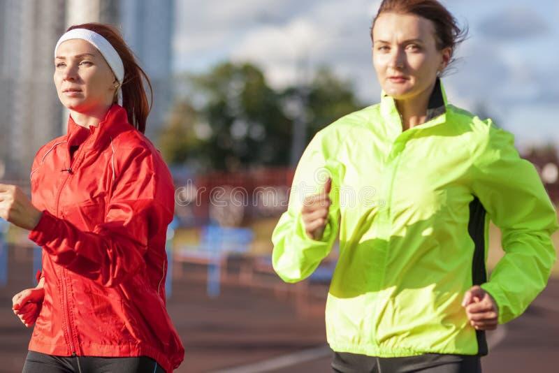Sport- och friidrottbegrepp Två Caucasian kvinnlig som har att jogga Excercises det fria arkivfoto