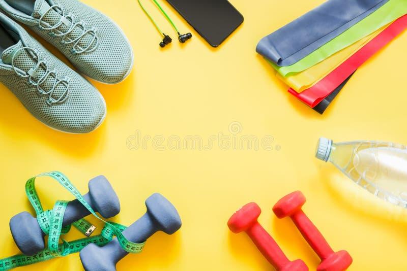 Sport- och konditionutrustning, hantlar, konditionskor som mäter bandet på punchy guling arkivbilder