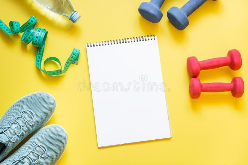 Sport- och konditionutrustning, hantlar, konditionskor som mäter bandet på punchy guling arkivbild
