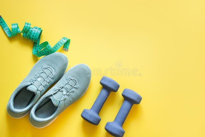 Sport- och konditionutrustning, hantlar, konditionskor som m?ter bandet p? punchy guling B?sta sikt, utrymme f?r text arkivbild