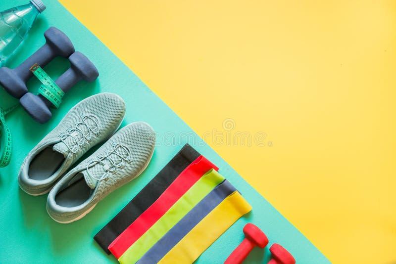Sport- och konditionutrustning, hantlar, konditionskor som m?ter bandet p? punchy guling royaltyfri fotografi