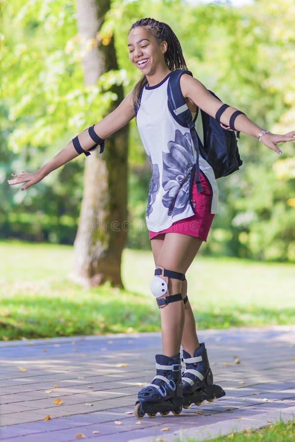 Sport- och livsstilbegrepp Afrikansk amerikantonåring som lär rullen som åker skridskor, medan balansera med händer arkivfoton