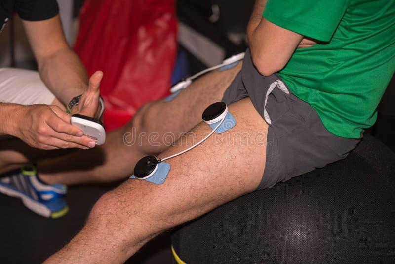Sport och muskulös rehabilitering: Yrkesmässig sjukgymnastikbehandling med Electrostimulation terapi på ben arkivbilder