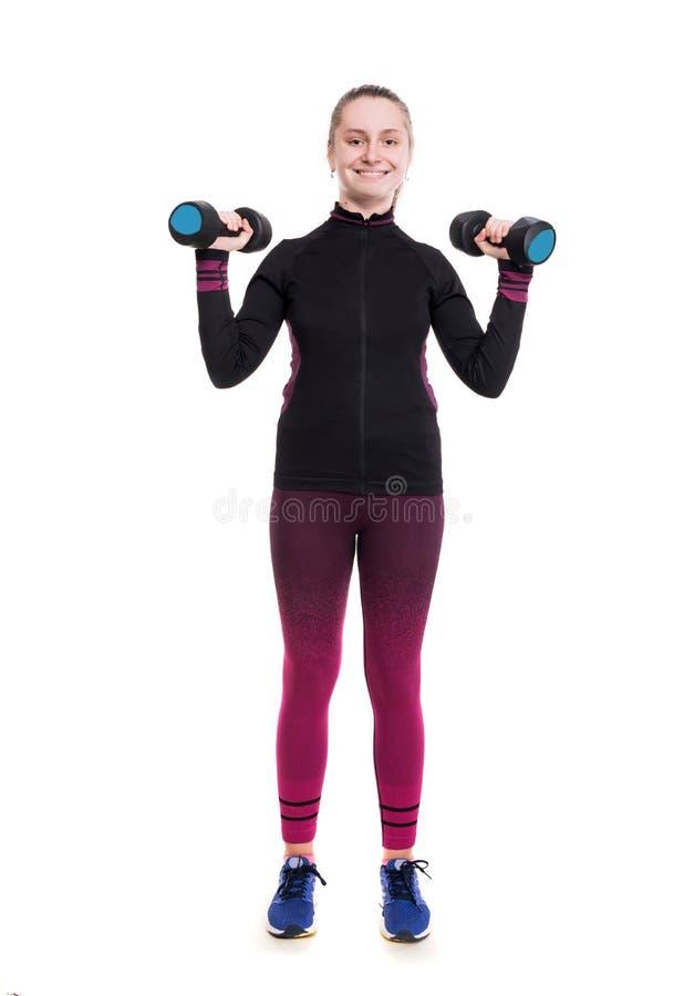 Sport- och sjukvårdbegrepp Le den tonåriga flickan i sportswear som utarbetar med hantlar i studio fotografering för bildbyråer