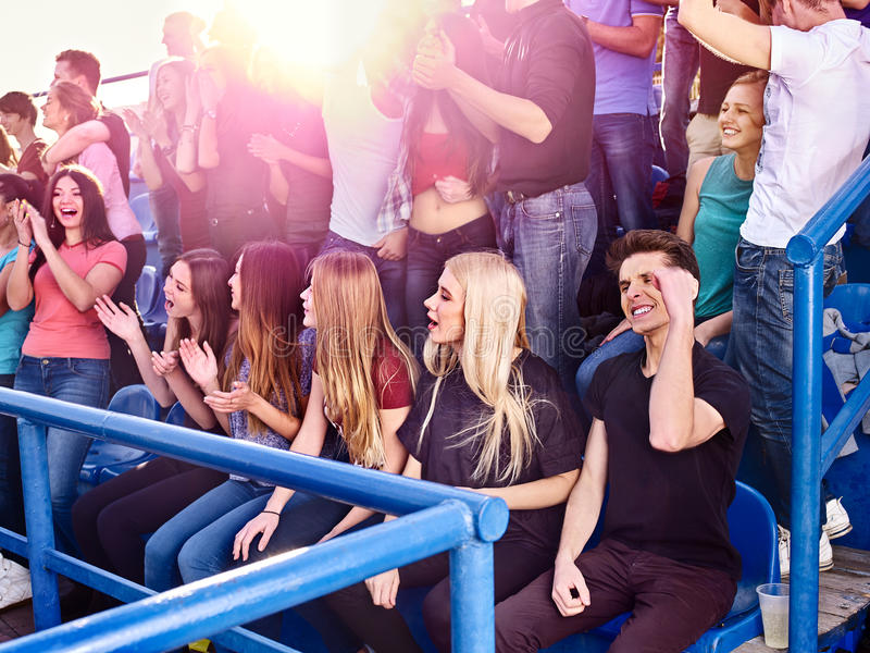 Sport olympiad fans singing on tribunes. Sport fans of olympiad singing on tribunes. Group people on olympiad in sun rays royalty free stock image