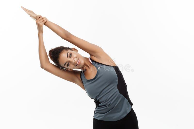 Sport, opleiding, levensstijl en Fitness concept - portret van mooie gelukkige Afrikaanse Amerikaanse vrouw het uitrekken zich ha stock fotografie