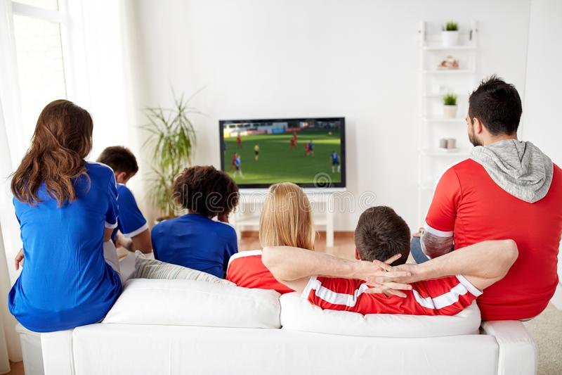 Football fans watching soccer game on tv at home. Sport, people and entertainment concept - friends or football fans watching soccer game on tv at home stock images