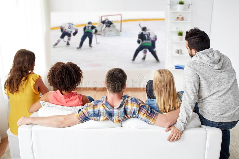 Friends watching ice hockey on projector screen royalty free stock photos