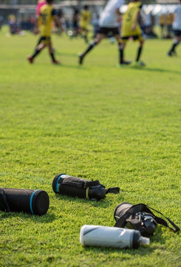 Sport plastic flessen zoet water verlaten op een voetbalgebied stock fotografie