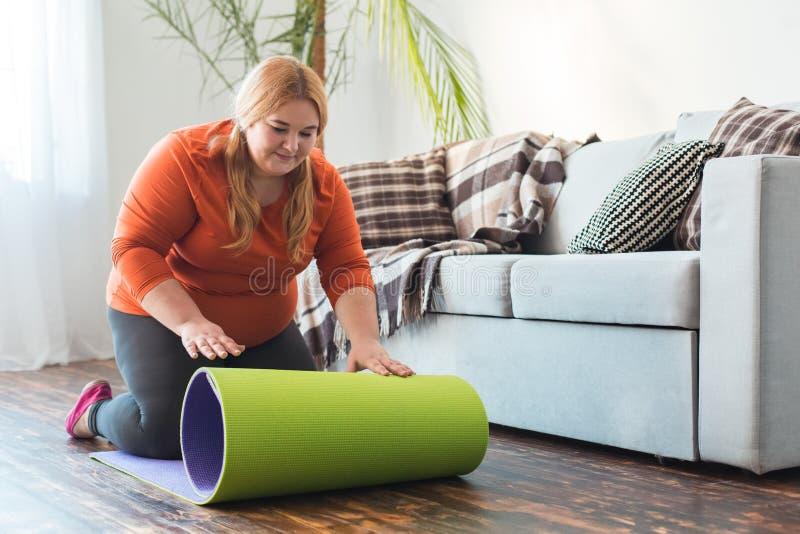 Sport potelé de femme à la maison reposant le tapis de roulement de yoga joyeux image stock