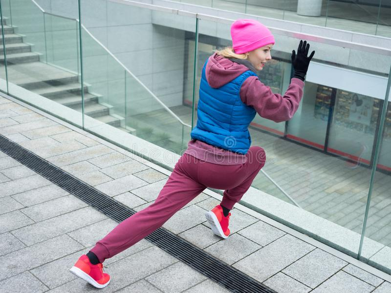 Sporty girl stretching outdoor on city street royalty free stock photo