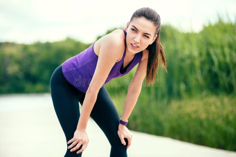 sport Ricreazione prima o dopo l'allenamento e funzionamento nel parco Bella donna sulla maglietta porpora sul fondo della natura immagini stock libere da diritti