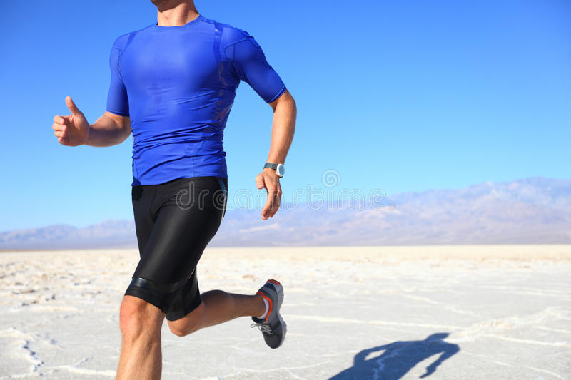 Sport - runner running in desert. Sport - runner running and sprinting in desert. Athlete man during sprint run at great speed. Fitness man wearing compression stock photography