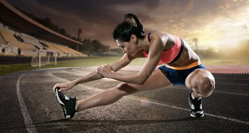 Sport. Runner stretching on the running track. The stadium on the background royalty free stock image